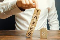 Houten blokken met de daling van woordbelastingen op een miniatuurhuis Het concept de belastingdruk op huisvesting, flat, bezit stock foto's