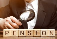 Houten blokken met het woordpensioen en een vergrootglas in de hand van een mens Analyse van pensioneringsbetalingen De grootte v royalty-vrije stock afbeeldingen