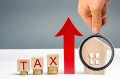 Houten blokken met muntstukken en de woordbelasting en een omhooggaande pijl naast het huis Het concept de groei van belastingen  royalty-vrije stock afbeeldingen