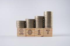 Houten blokkennummer 2017 met gestapelde zilveren muntstukken op houten blok Stock Fotografie