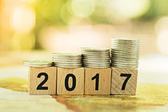 Houten bloknummer 2017 met stapelmuntstukken die als nieuw jaar als achtergrond of bedrijfsconcept gebruiken Royalty-vrije Stock Afbeelding