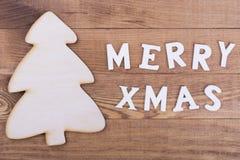 Houten boom met Vrolijke Kerstmiswoorden Stock Fotografie