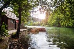 Houten boot bij de pijler op het mooie duidelijke meer in het hout Plitvice, Nationaal Park, Kroatië stock foto