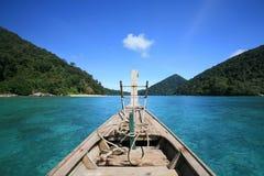Houten boot die op transparante blauwe overzees vaart royalty-vrije stock foto