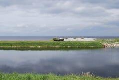 Houten boot op de het meerkust van Meerpeipsi Chudskoe, bewolking royalty-vrije stock foto's