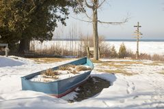 Houten boot op oever van Dwarsstad, Michigan in de winter Stock Foto's