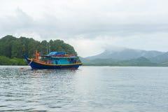Houten boot in overzees met berg en wolkenachtergrond Stock Afbeeldingen