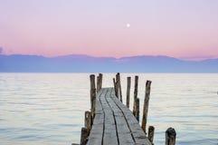 Houten bootdok met de zonsonderganghemel op de achtergrond in Meer Atitlan, Guatemala stock foto's