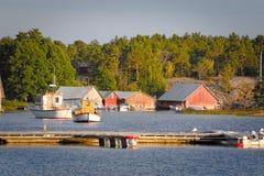 Houten botenhuizen bij zonsondergang in Aland-archipel, waar de aard wordt overdreven stock foto's