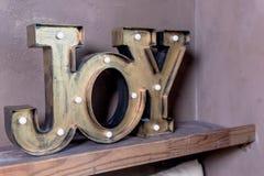 Houten brieven die die woordvreugde vormen op grijze muur wordt geschreven De prentbriefkaar van Kerstmis De inschrijving: Vreugd stock afbeelding