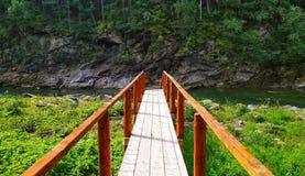 Houten brug in de bergrivier met rotsen op de achtergrond stock afbeelding