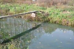 Houten brug met bezinning in water Stock Foto's