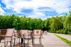Houten brug met een omheining waarop de lijsten en de stoelen worden gevestigd De zomerkoffie Het is buiten de zomer De zon glans royalty-vrije stock afbeeldingen