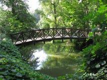 Houten brug met traliewerk boven de rivier in het park onder de bomen Uman de Oekraïne stock afbeelding