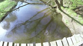 Houten brug op een kleine rivier stock footage