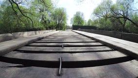 Houten brug op een kleine rivier stock videobeelden