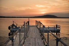 Houten brug op het strand en mooie zonsondergang dichtbij het overzees Stock Foto