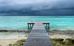 Houten brug op strand dat in het overzees wordt uitgebreid Stock Foto's