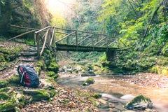 Houten brug over beek in de herfstbos met rugzak in voorgrond Lange Blootstelling Exploratieconcept, aard het volgen, reis stock fotografie