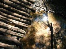 Houten brug over een kleine bosstroom Brug van logboeken en de zandige bodem van de stroom royalty-vrije stock fotografie