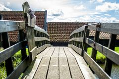 Wooden bridge crossing the water. On a sunny day. An entrance to a famous windmill Royalty Free Stock Photography