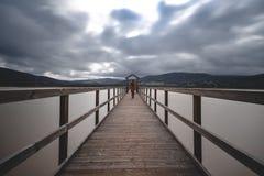 Houten brug over meer bij de bewolkte dag lange blootstelling royalty-vrije stock afbeeldingen