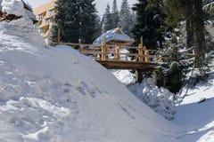 Houten brug tussen oude houten plattelandshuisjes in een snow-covered skii Stock Afbeelding