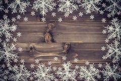 Houten bruine Kerstmisachtergrond en witte sneeuwvlokken met spac royalty-vrije stock afbeelding