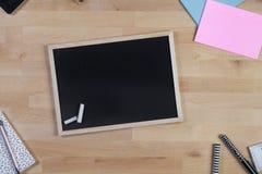 Houten Bureau met bord, blocnote en pennen Hoogste mening royalty-vrije stock foto's