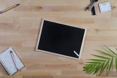 Houten Bureau met bord, blocnote en pennen Hoogste mening stock fotografie