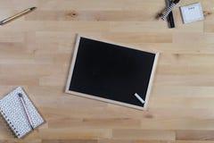 Houten Bureau met bord, blocnote en pennen Hoogste mening stock foto's
