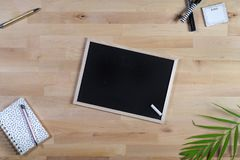 Houten Bureau met bord, blocnote en pennen Hoogste mening royalty-vrije stock fotografie
