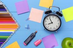 Houten bureau met kantoorbehoeften en lege stickers, wekker en appel Conceptuele achtergrond in de stijl van terug naar Stock Foto