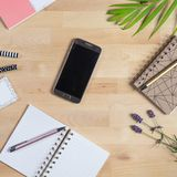 Houten Bureau met slimme telefoon, blocnote en pennen Hoogste mening royalty-vrije stock foto