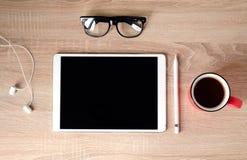 Houten bureau Witte tablet met zwart-omrande glazen Kop thee stock foto's