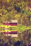 Houten cabine in bos op meerkust, Noorwegen Stock Afbeelding