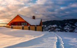 Houten chalet in diepe sneeuw bij zonsopgang stock foto's