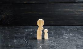 Houten cijfers van moeder en kind De baby is gescheiden van het moederslichaam Het concept rijping en onafhankelijkheid stock foto's