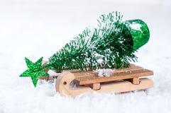 Houten de winterar die een kleine Kerstboom dragen Stock Foto's