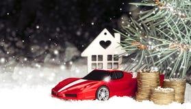Houten decoratief huis in de sneeuw, auto, muntstukken Stock Foto