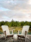 Houten dek met stoelen en bos op achtergrond Stock Afbeeldingen