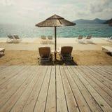 Houten dekterras over overzeese strand en hemel De achtergrond van de de zomervakantie Stock Foto's