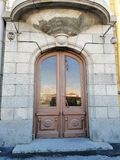 Houten deur bij het gebouw met lantaarns en de bezinning van de dijk in glas royalty-vrije stock afbeelding