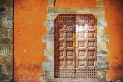 Houten deur in een oranje muur stock afbeeldingen