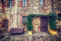 Houten deur en bank in Monteriggioni stock foto