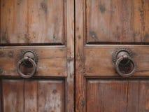 Houten deur en ijzerhandvatten in Toscanië Stock Afbeelding