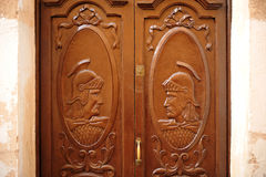 Houten deur met cijfers van Roman militairen, Caceres, Spanje Stock Foto's