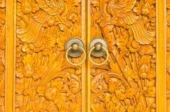 Houten deur van buitenhuis met gesneden ornament Stock Afbeeldingen