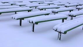 Houten die Banken in een Park volledig door Sneeuw na Zware Sneeuwval wordt behandeld stock videobeelden