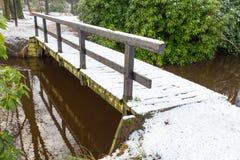 Houten die brug met sneeuw in de winter wordt behandeld Royalty-vrije Stock Afbeeldingen
